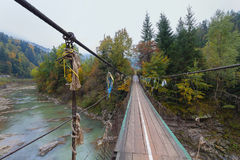 Suspended wooden bridge over a mountain river Royalty Free Stock Photography