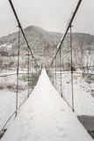 Suspended wooden bridge over a winter mountain river. Royalty Free Stock Photography