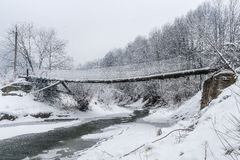 Suspended wooden bridge over a winter mountain river. Stock Image