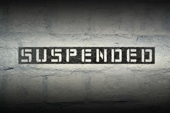 Suspended WORD GR. Suspended stencil print on the grunge white brick wall stock photography
