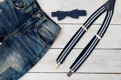 Suspenders and bow tie on wooden background. Kids fashion. Flat lay stock image
