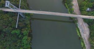 Suspendierungssteg über dem Fluss zwischen der Stadt und dem Wald stock video
