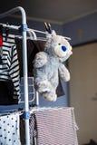 Suspensão cinzenta do urso de peluche seca na cremalheira com roupa foto de stock royalty free