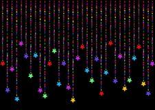 A suspensão colorida stars em um fundo preto Foto de Stock