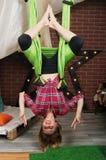 Suspensão da menina de cabeça para baixo em uma rede para a ioga Foto de Stock