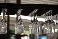 Suspensão dos vidros de cabeça para baixo no suporte de copo da barra Fotografia de Stock