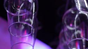 Suspensão dos vidros de vinho de cabeça para baixo acima de uma cremalheira da barra filme
