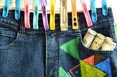Suspensão e pregadores de roupa de umas calças das calças de brim com bancos dos dólares fotos de stock royalty free