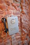 Suspensão em um telefone retro velho da parede de tijolo fotos de stock royalty free