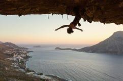 Suspensão fêmea do montanhista de rocha de cabeça para baixo na rota de desafio na caverna no por do sol fotos de stock