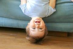 Suspensão pequena engraçada bonito do bebê de cabeça para baixo no sofá que olha a câmera, sorrindo Foto de Stock Royalty Free