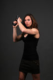 Suspense. Female model posing in contemporary clothes with a handgun Royalty Free Stock Photos