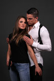 Suspense. Couple posing in contemporary clothes with woman holding a handgun Royalty Free Stock Images