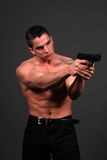 Suspense. Male model posing in contemporary clothes with a handgun Stock Images