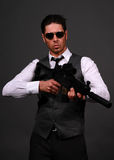 Suspense. Male model posing in contemporary clothes with a rifle Stock Photos