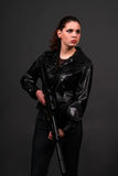 Suspense. Female model posing in contemporary clothes with a rifle Royalty Free Stock Photography