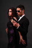 Suspense Romance. Couple posing in contemporary clothes with man holding a handgun Stock Images