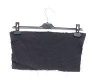 Suspensión de ropa plástica con la ejecución en ella un pedazo de paño negro Imagen de archivo libre de regalías