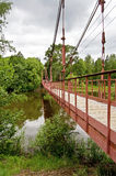 Suspension bridge. Red suspension bridge through small river Sherna, Russia royalty free stock photography