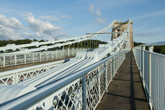 Suspension bridge. The steel plate chains leading to a supporting tower on the Menai suspension, Gwynedd, Wales, UK, with a walkway against a blue sky Stock Images