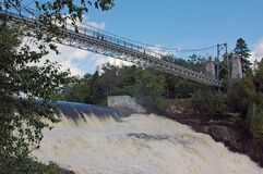 Montmorancy Falls suspension bridge. Bridge hangs suspended over rushing white water of Montmorancy Falls with blue sky scattering of clouds and verdant growth Royalty Free Stock Photos