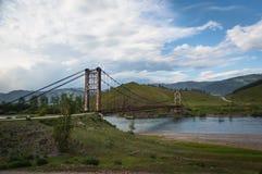 Suspension bridge across mountain river. Evening light, blue sky Stock Photos