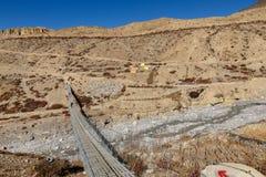 Suspension bridge across mountain river, Himalayas. Nepal Royalty Free Stock Photos