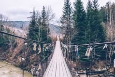 Suspension bridge across mountain river. Journey through the Carpathian mountains in Eastern Europe. Suspension bridge over the spring river Dniester. Rustic old Royalty Free Stock Photo