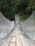 Suspension bridge across mountain river. Shallow depth of field. Focus in the the middle of the bridge Royalty Free Stock Images