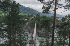 Suspension bridge across the mountain river to the church. Old bridge from one bank to another to the nunnery Royalty Free Stock Photo