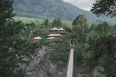 Suspension bridge across the mountain river to the church. Old bridge from one bank to another to the nunnery Stock Images