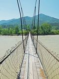Suspension bridge across the river Royalty Free Stock Photo