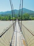 Suspension bridge across the river. Suspension bridge across the broad river Royalty Free Stock Photo