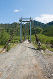 Suspension bridge across the river in the mountains Stock Photo
