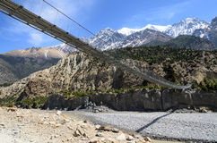 Suspension bridge across the river in mountains Stock Image