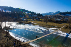 Suspension bridge across the river. People walking on a suspension bridge across the river. Beautiful mountain river.Spring came Royalty Free Stock Images