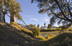Suspension bridge across the river and the temple. On the shore Royalty Free Stock Photography