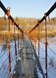Suspension bridge across the river in winter. In winter, a suspension bridge across the river Miass in Chelyabinsk, very dangerous, Skolsky, moving on which Royalty Free Stock Image
