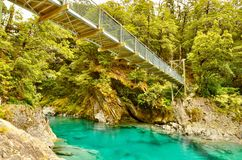 Suspension Bridge along the Blue Pools Nature Track, New Zealand. Looking over turquoise blue waters of the Makarora River from the popular Blue Pools Track in royalty free stock images