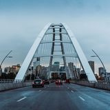 Suspension bridge archway with road. Roadway entering a suspension bridge archway. Early morning or evening time of day with some cloudy overcast skies. Very stock photo