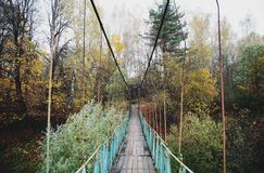 Suspension bridge in autumn forest. Beautiful autumn photo with a pendant blue bridge in autumn colorful forest Royalty Free Stock Images