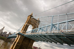 Suspension Bridge In Cincinnati Ohio. Image of Cincinnati skyline and historic suspension bridge cross Ohio River on an overcast day. The historic John A Stock Images