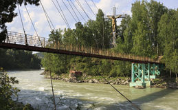 Suspension Bridge and cross with a crucifix on the island. Of the Katun River. Altai royalty free stock photography