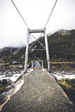 Suspension bridge crossing river shot in portrait format. Stock Photography