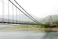 The Suspension Bridge on Foggy Fairyland of Dongjiang River. Is like the Chinese traditional ink and wash landscape painting, located in Zixing City, Hunan stock photography