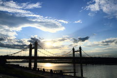 Suspension Bridge in the late clouded evening Stock Photos
