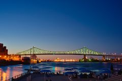 Suspension Bridge in Montreal Canada. At night with the reflections of lights on the water. This is a long exposure shot with a clear sky, no clouds royalty free stock photo