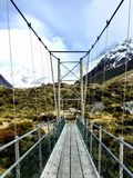 Suspension Bridge leading to Snowy Mountains. Suspension Bridge in Mount Cook National Park leading along the hiking trail with snowy mountains in the background royalty free stock image