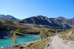 Suspension bridge through the mountain river Stock Photo