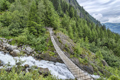 Suspension bridge over fast mountain river Stock Photography